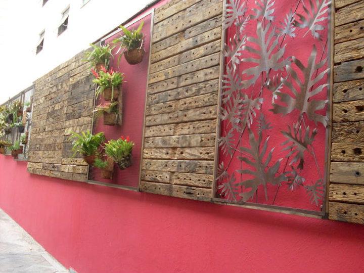 Muro vermelho com planta e madeira