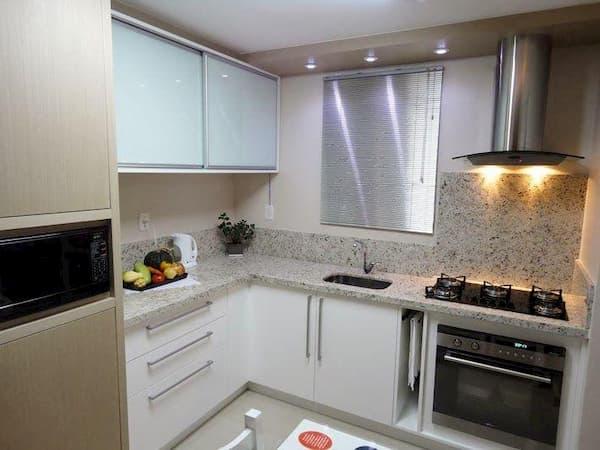 Cozinha com bancada e frontões em granito branco marfim