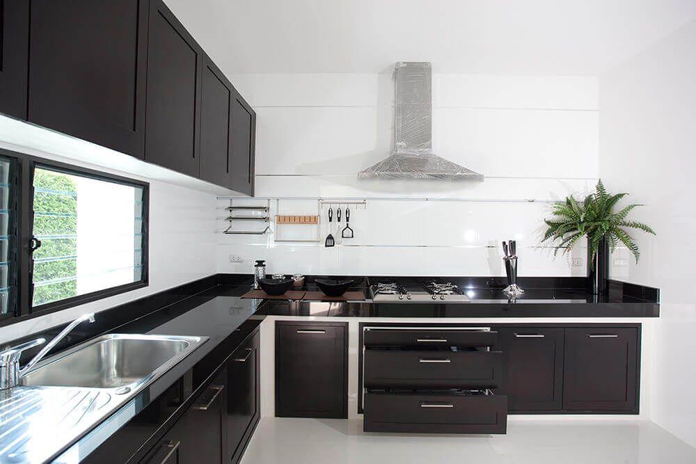 cozinha moderna com moveis pretos e parede clara